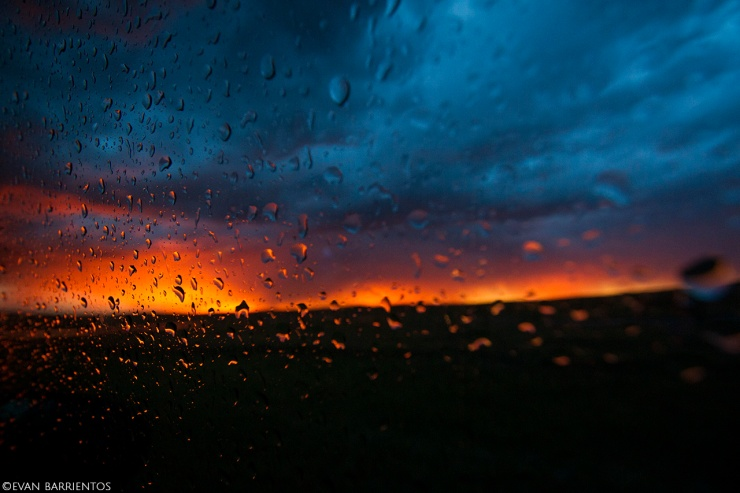 Raindrops on a window looking out to a prairie at sunset.
